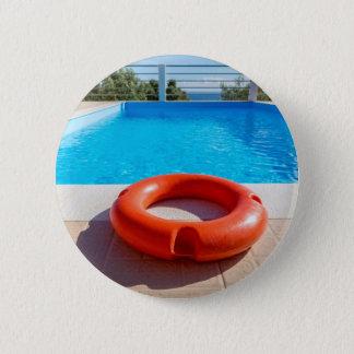 Orange life buoy at blue swimming pool 6 cm round badge