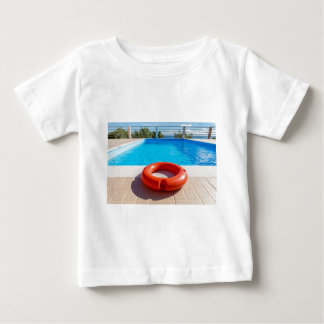 Orange life buoy at blue swimming pool baby T-Shirt