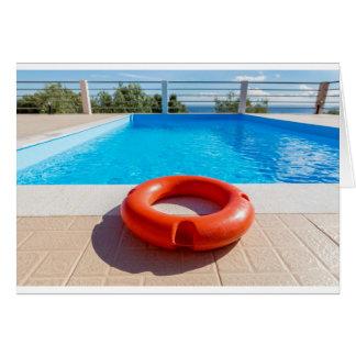 Orange life buoy at blue swimming pool card