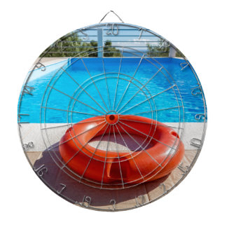 Orange life buoy at blue swimming pool dartboard with darts