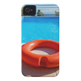 Orange life buoy at blue swimming pool iPhone 4 covers