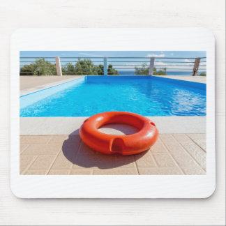 Orange life buoy at blue swimming pool mouse pad