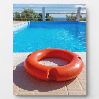 Orange life buoy at blue swimming pool plaque