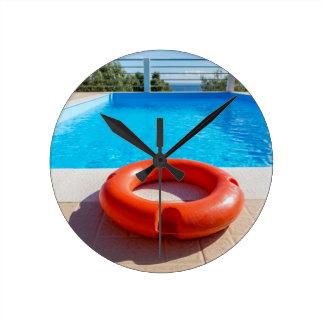 Orange life buoy at blue swimming pool round clock