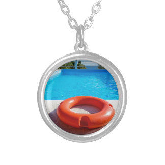 Orange life buoy at blue swimming pool silver plated necklace