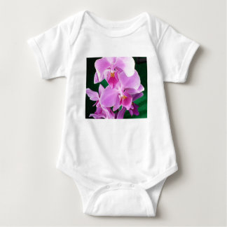 Orchid blooms closeup in pink baby bodysuit