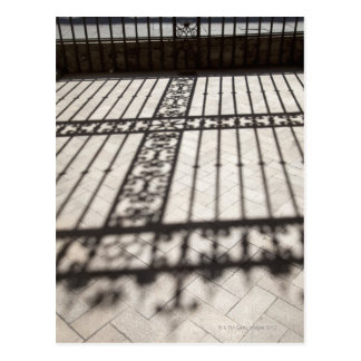 ornate iron fencing shadow on tile floor postcard