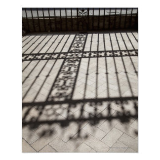 ornate iron fencing shadow on tile floor poster