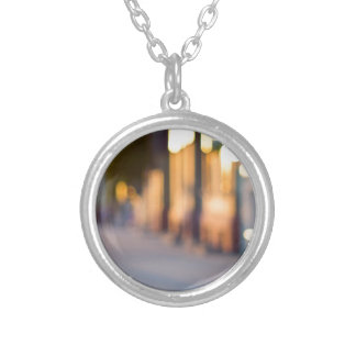 Out of focus image of streets and buildings silver plated necklace