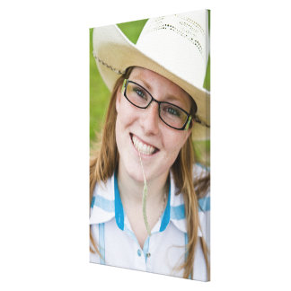 Outdoor portrait of smiling cowgirl biting grass gallery wrap canvas
