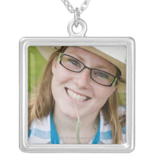 Outdoor portrait of smiling cowgirl biting grass silver plated necklace