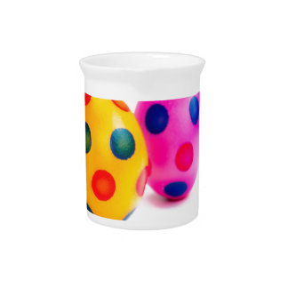 Painted easter eggs in row on white background pitcher