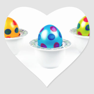 Painted easter eggs standing in porcelain egg cups heart sticker