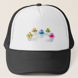 Painted easter eggs standing in porcelain egg cups trucker hat