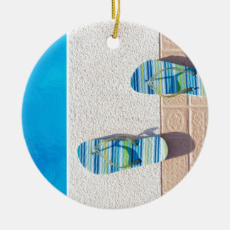 Pair of slippers at edge of swimming pool ceramic ornament