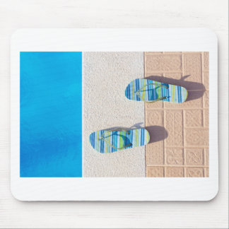 Pair of slippers at edge of swimming pool mouse pad