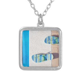 Pair of slippers at edge of swimming pool silver plated necklace