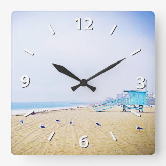Pale blue sky and light golden sandy beach photo square wall clock
