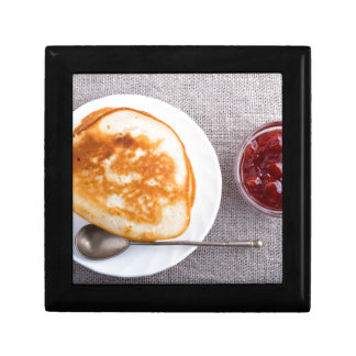 Pancakes and a glass cup with strawberry jam gift box