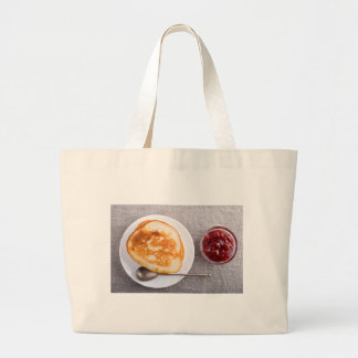 Pancakes and a glass cup with strawberry jam large tote bag