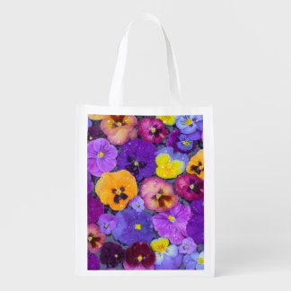 Pansy flowers floating in bird bath with dew reusable grocery bag