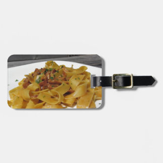 Pappardelle with mushrooms on rustic outdoor table luggage tag