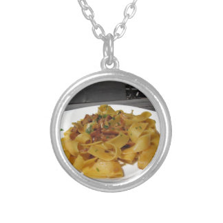 Pappardelle with mushrooms on rustic outdoor table silver plated necklace