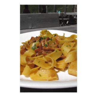 Pappardelle with mushrooms on rustic outdoor table stationery