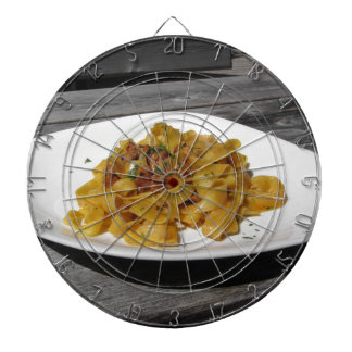 Pappardelle with mushrooms on rustic wooden table dartboard