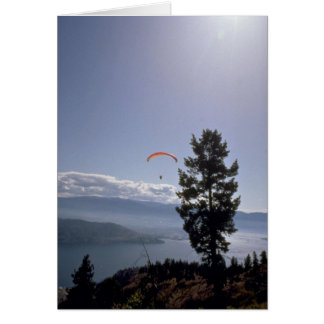 Paraglider flying over valley lake card
