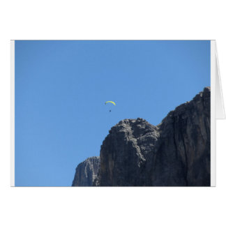 Paraglider with his yellow parachute near mountain card