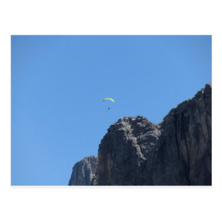 Paraglider with his yellow parachute near mountain postcard