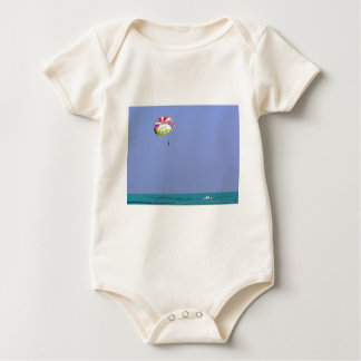 Parasailing over the blue water baby bodysuit
