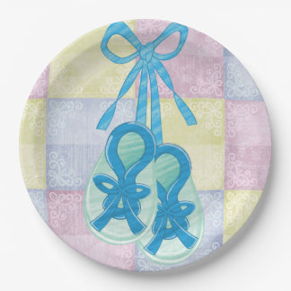 Pastel quilt and baby booties on paper plates