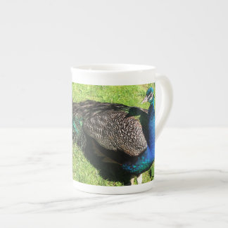 Peacock on green grass tea cup