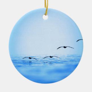 Pelicans flying over ocean ceramic ornament