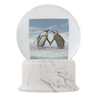Penguins couple snow globes
