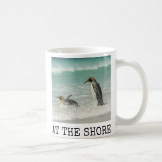 Penguins swimming on the beach coffee mug