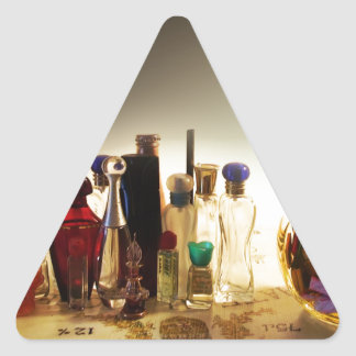 Perfumes and candies on a table triangle sticker