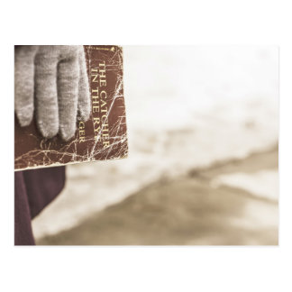person in glove and old novel postcard