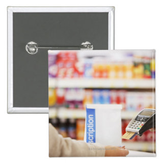 Pharmacist holding security device for customer 15 cm square badge