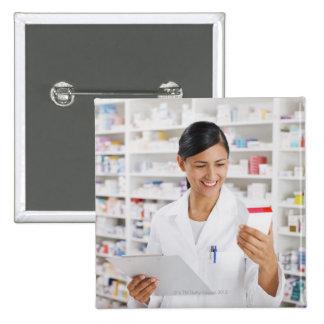 Pharmacist in drug store holding clipboard 15 cm square badge