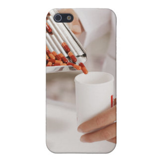 Pharmacist in drug store measuring pills into iPhone 5 case