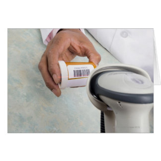 Pharmacist scanning pill bottle with a barcode card