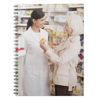 Pharmacist talking to customer in drug store notebook