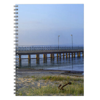 Photo of pier in sunset with anchor notebooks