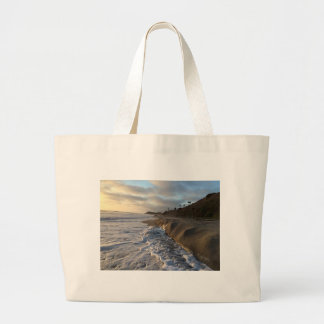 Photograph of the waves hitting the sand large tote bag