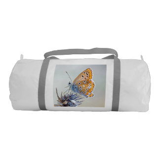 Photography of butterfly on flower of the desert gym duffel bag