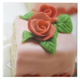 Piece of birthday cake with marzipan roses on large square tile