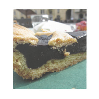 Piece of chocolate cake on green paper napkin notepad